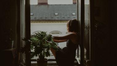 Frau mit Schwangerschaftsdepressionen sitzt am Fenster