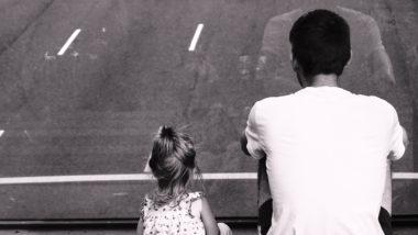 Vater und Tochter sitzen zusammen und schauen auf die Straße