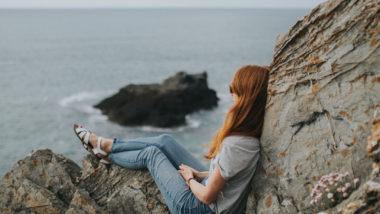 Frau mit einer Blasenmole sitzt am Meer