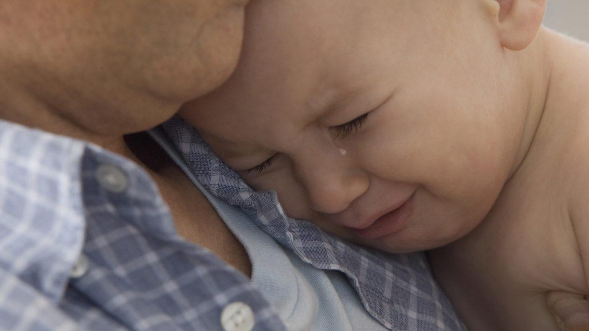 Kleiner Junge weint auf dem Arm seines Vaters