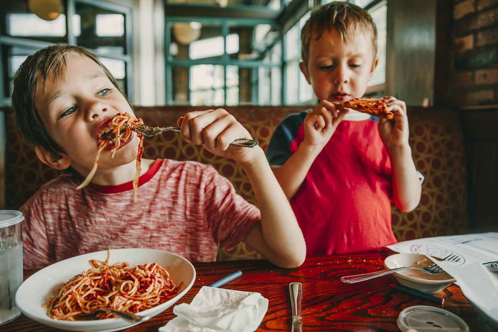 Kinder essen in einem Restaurant Pizza und Pasta