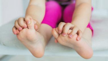 Ein Kleinkind fasst mit den Händen an seine Füße.