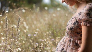 Schwangere Frau steht auf einer Wiese