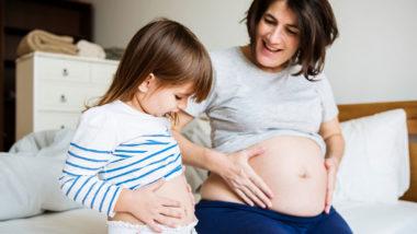 Schwangere Frau vergleicht ihren Bauch mit dem ihrer kleinen Tochter