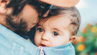 Vater trägt Baby in einem Tuch