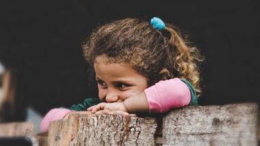 Kleines Mädchen grinst frech