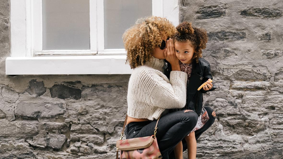 Mutter flüstert ihrer Tochter etwas ins Ohr