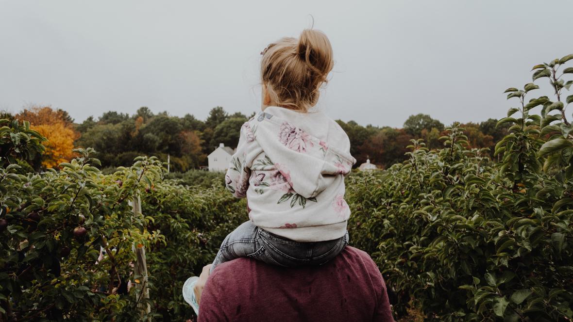 Vater trägt Tochter auf den Schultern