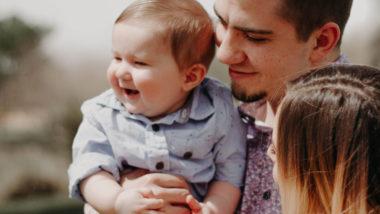 Vater und Mutter tragen Baby am Arm