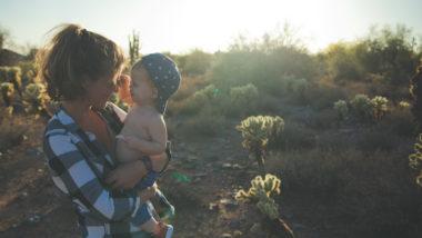 Tante und Baby stehen in der Natur.
