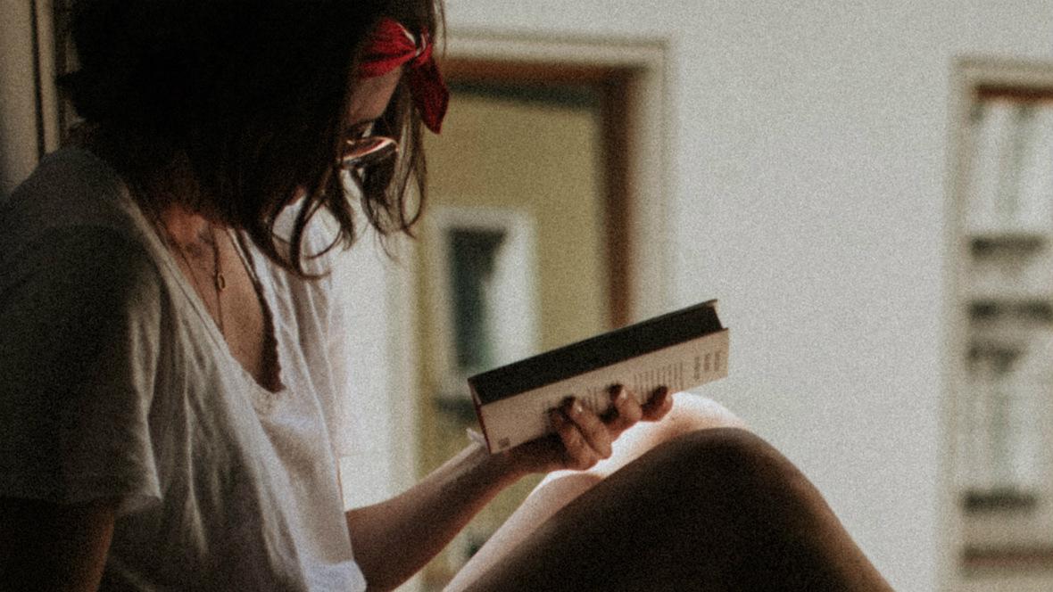 Frau sitzt am Fenster und ließt ein Buch.