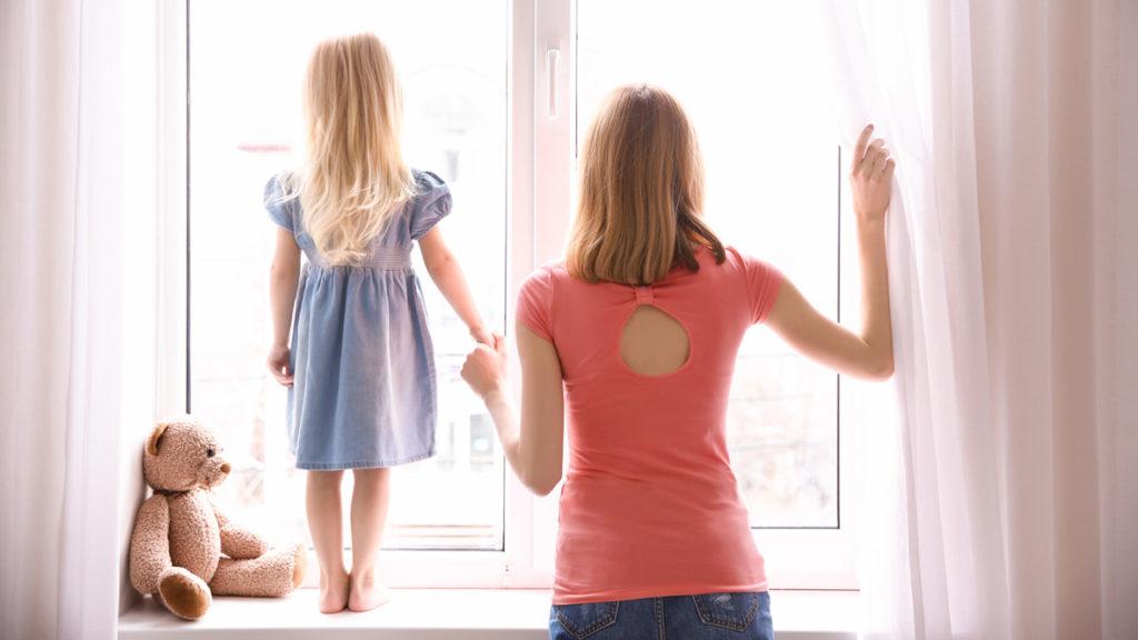 Mutter und Tochter stehen erwartunsvoll am Fenster