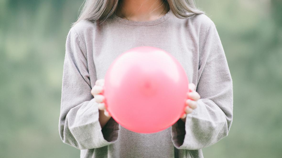 Junge Frau hält pinken Luftballon