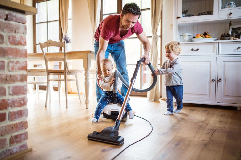 Vater und zwei Kleinkinder saugen Staub