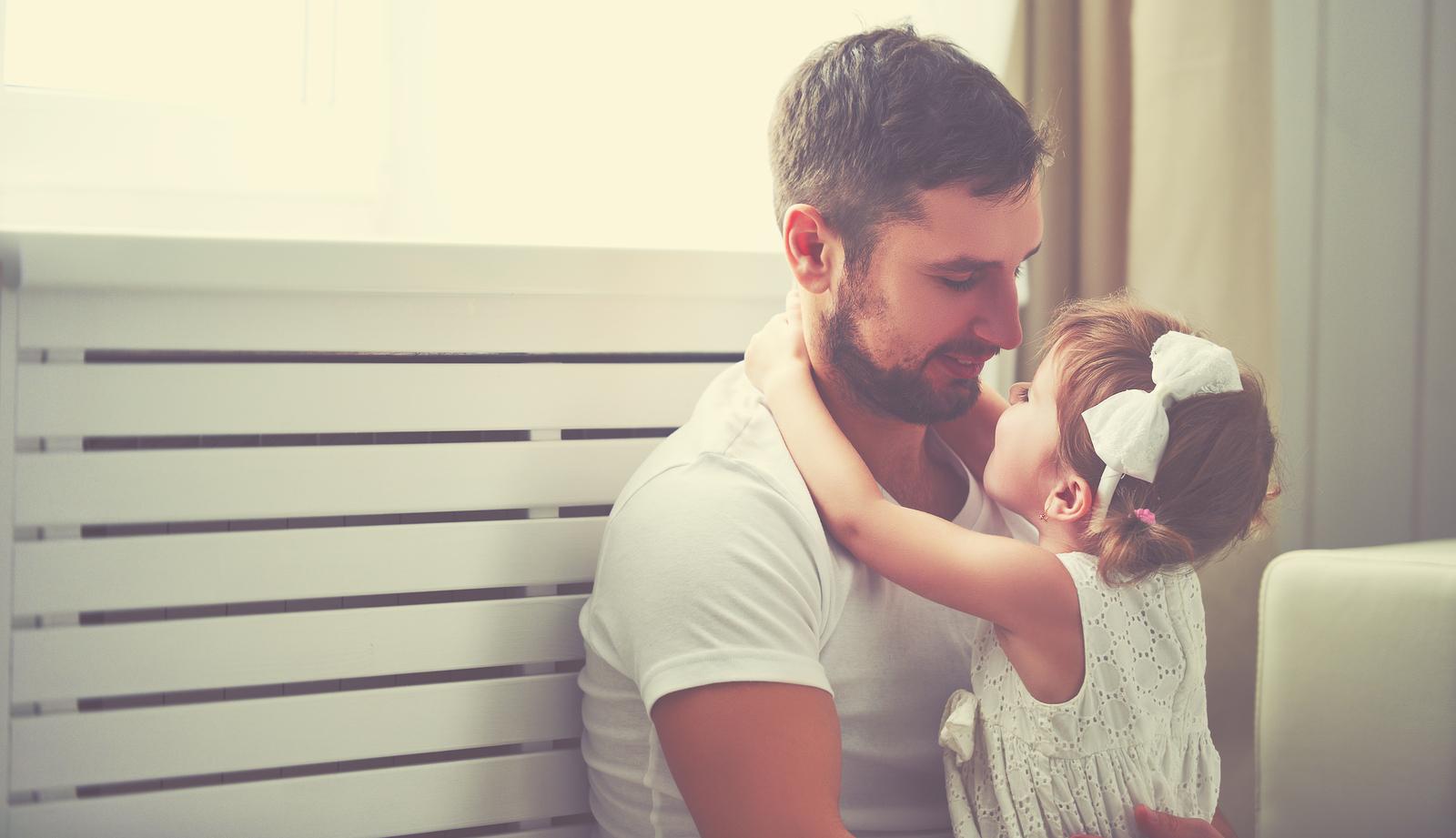 Vater sitzt mit Tochter auf dem Boden