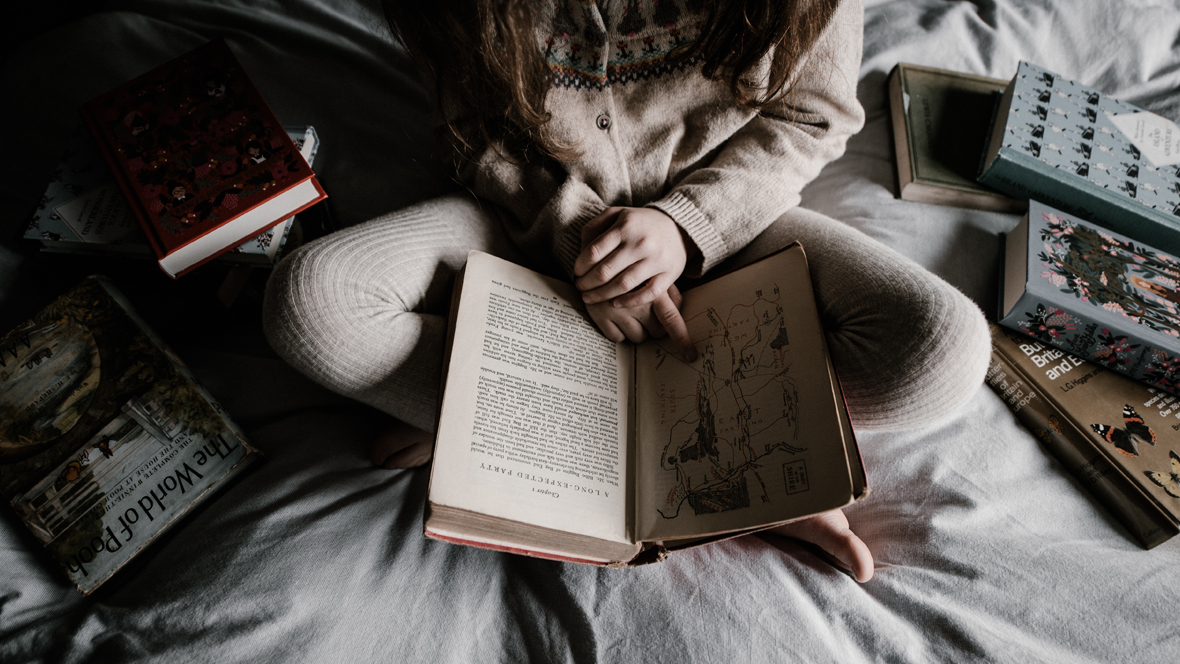 Mädchen sitzt im Bett und macht Hausaufgaben