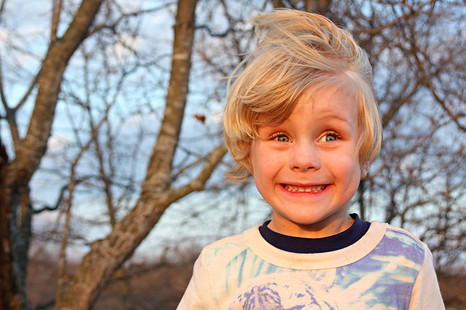 Kleiner Junge steht im Wald und lacht