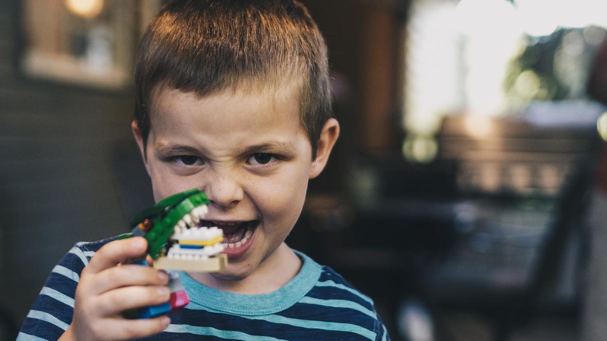 Kind spielt mit einem Plastikkrokodil