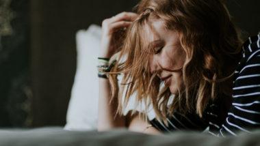 Junge Frau liegt müde auf dem Bett