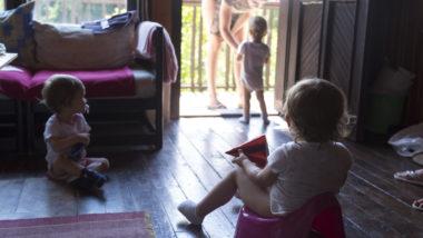 Familie mit drei Kindern spielt im Wohnzimmer