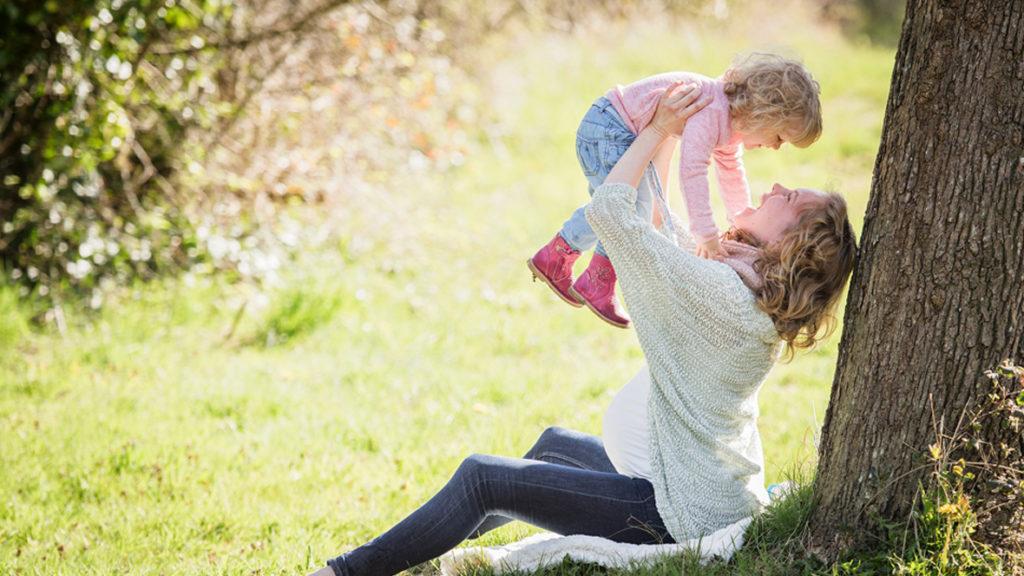 Frau hebt Kind in die Luft