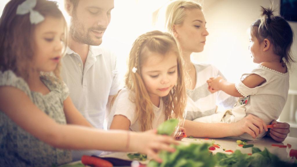 Familie mit drei Kindern kocht zusammen