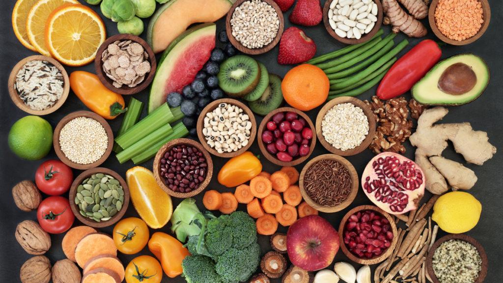 verschiedenes Obstm gemüse und Getreide auf einer schwarzen Platte