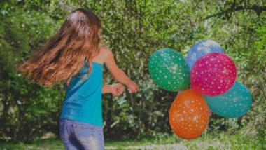 Mädchen spielt mit bunten Luftballons