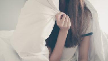 Junge Frau versteckt sich unter Bettdecke