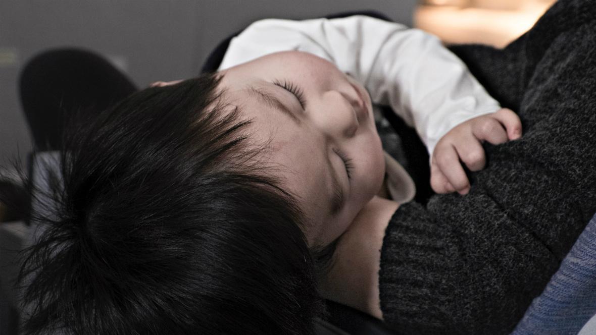 Ein Kind schläft ein den Armen