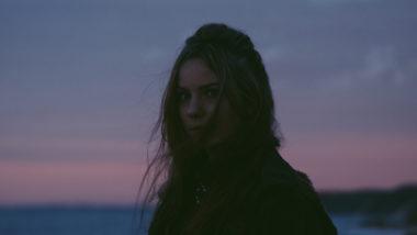 Frau steht im Sonnenuntergang