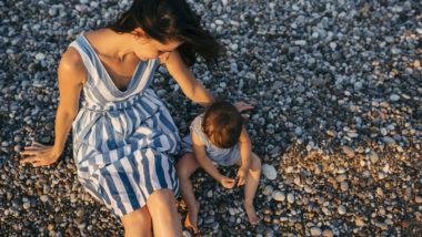 Mutter und Kind sitzen am Strand