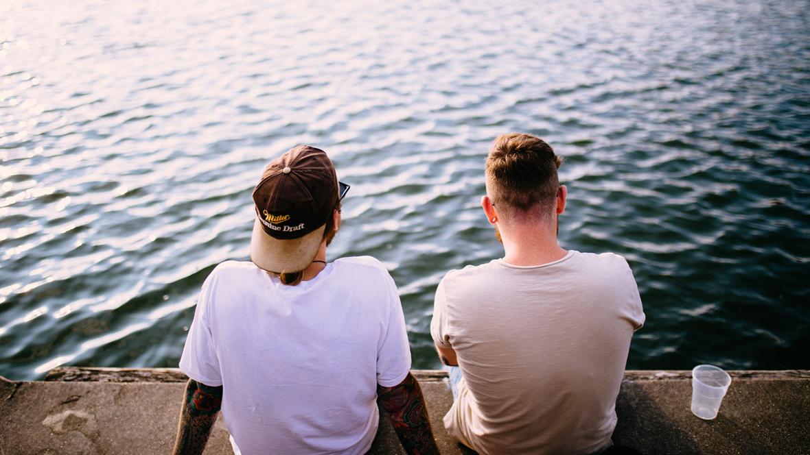 Freunde sitzen am Wasser und trinken Bier