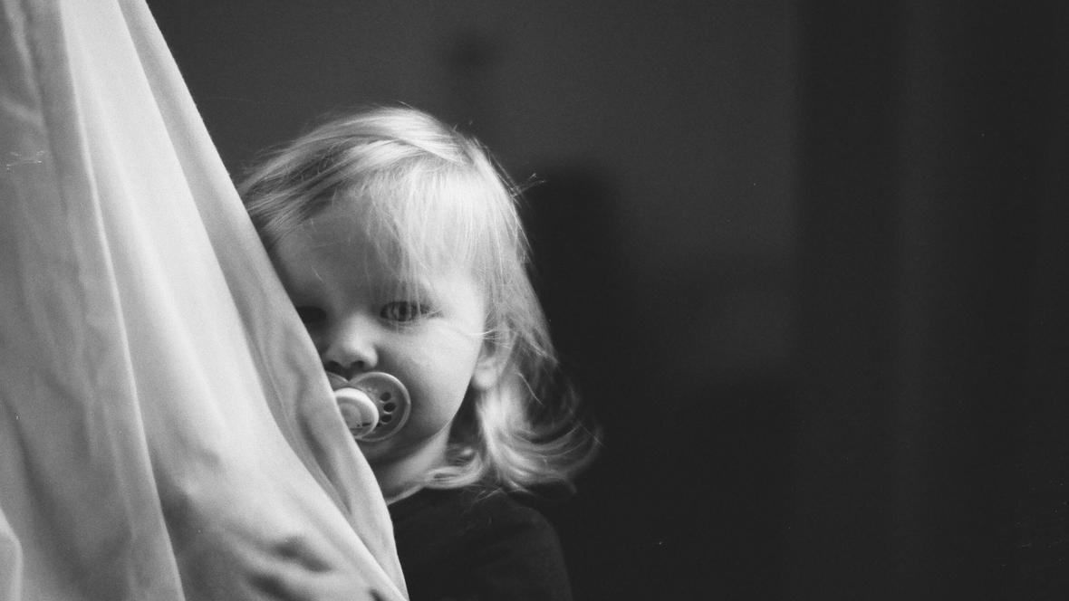 Kind versteckt sich hinter einem Vorhang