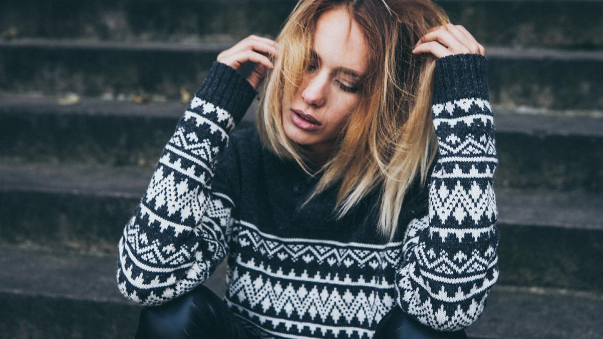 verzweifelte junge Frau sitzt auf Steintreppe
