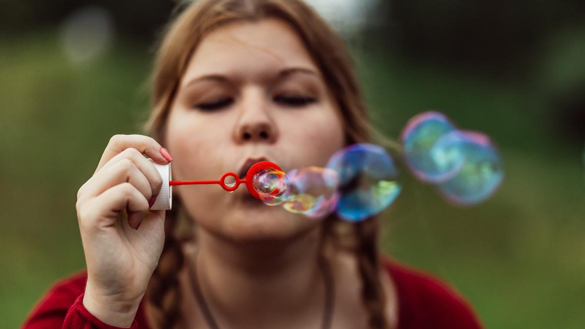 Junge Frau macht Seifenblasen