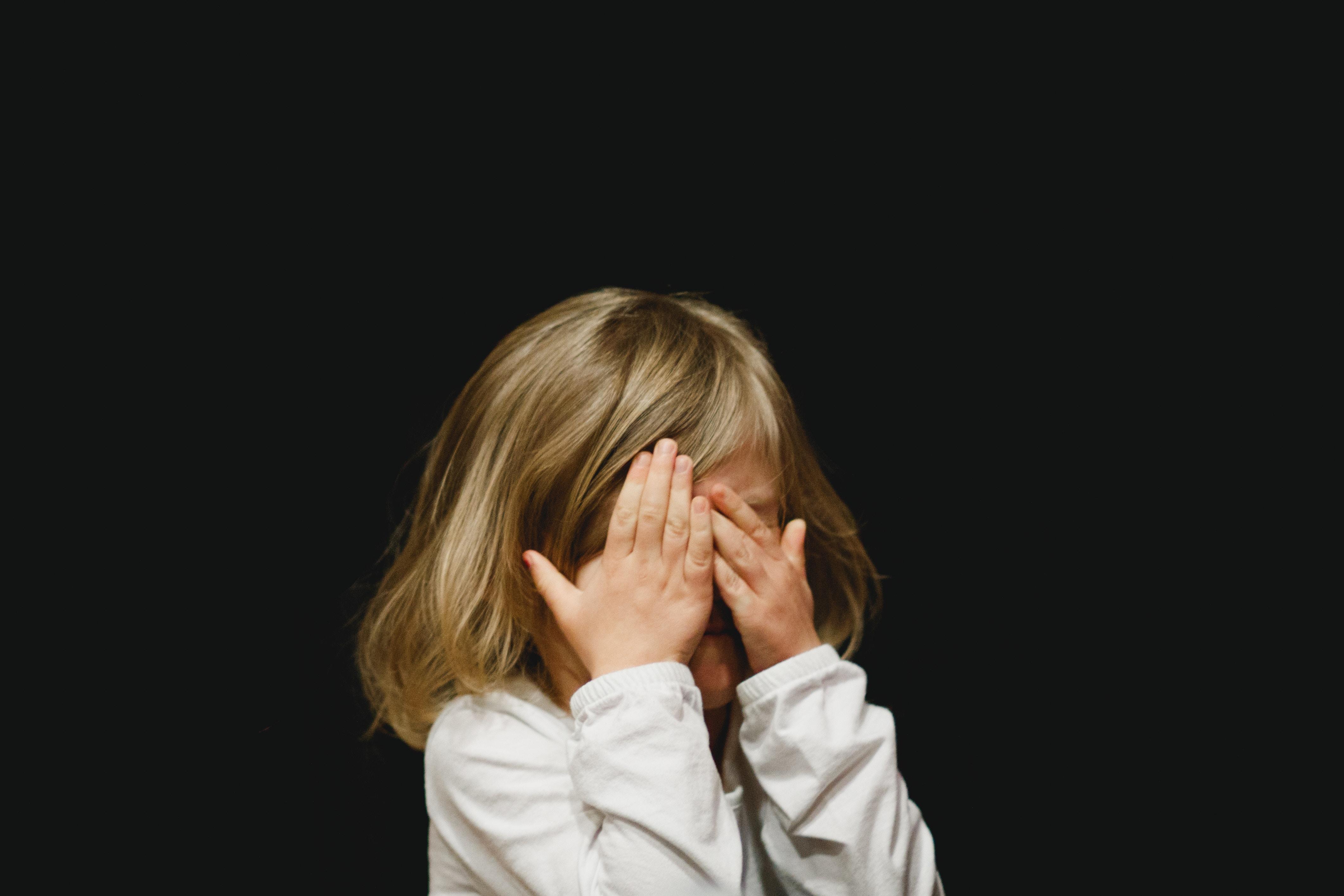Oh nein, Läuse! Ein Kind verbirgt sein Gesicht hinter den Händen