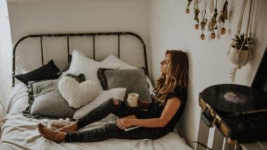Frau sitzt nach einer Ausschabung auf dem Bett