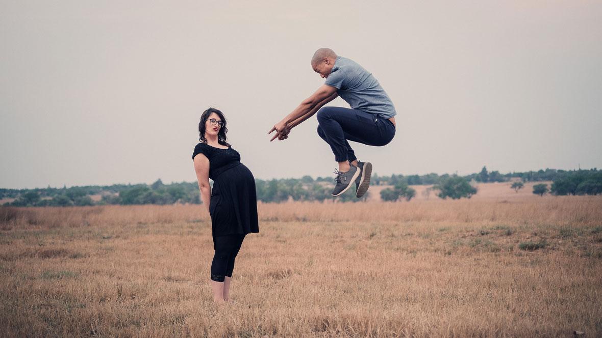 Frau in der 30. SSW steht mit ihrem Babybauch auf einem Feld, Mann springt in die Luft