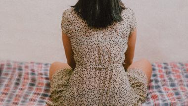 Rücken einer jungen Frau im gepunkteten Kleid