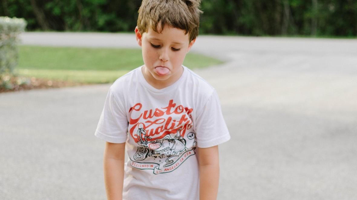 Junge streckt gelangweilt die Zunge heraus