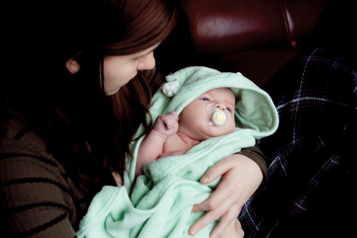 Ein frisch gebadetes Baby liegt im Arm seiner Mutter - so macht Babypflege Freude