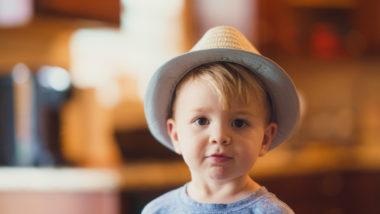 Ein kleiner Junge mit Hut schaut in die Kamera