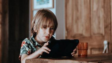 Kind spielt an einem Tablet