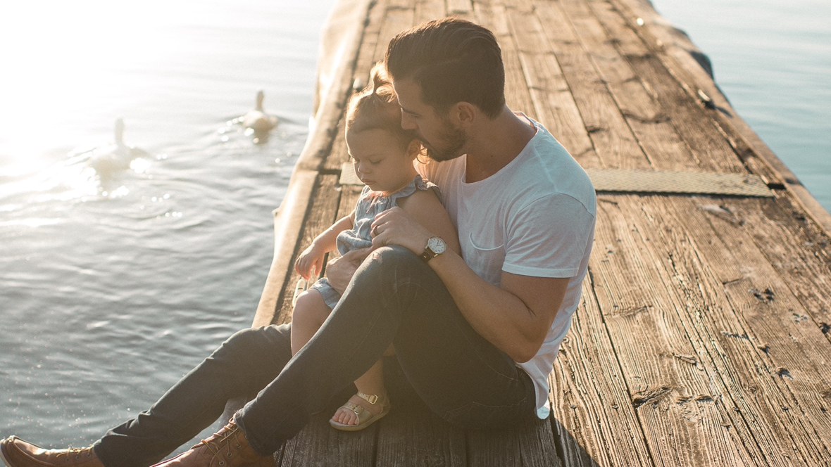 VAter und Tochter sitzen auf einem Steg