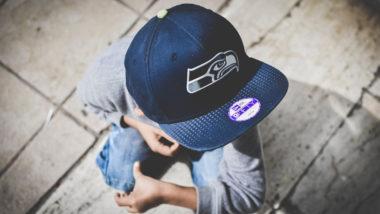 Kind mit einer Mütze sitzt auf der Straße