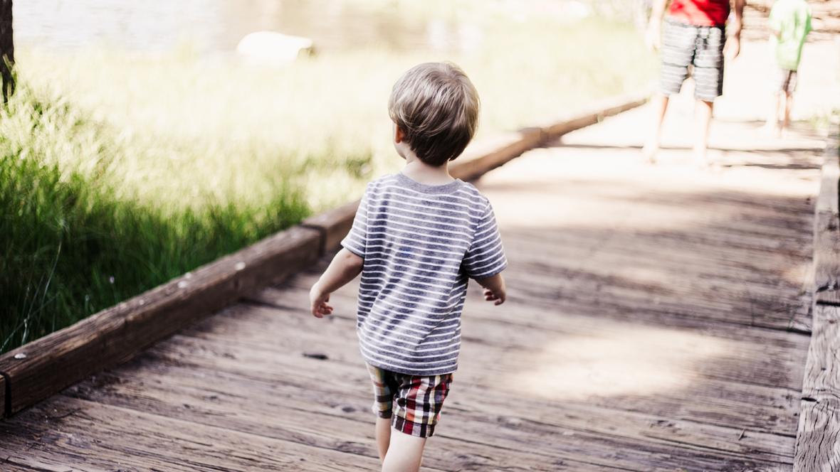 Kleiner Junge läuft über Holzsteg