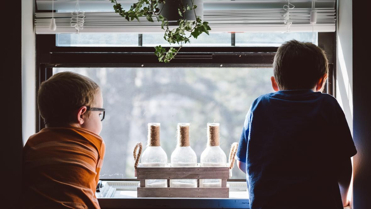 Kinder stehen am Fenster und schauen raus