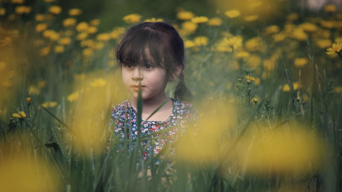 Mädchen steht in blühender Blumenwiese