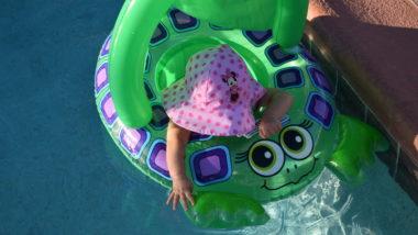 Baby sitzt in Schwimmhilfe in Froschform
